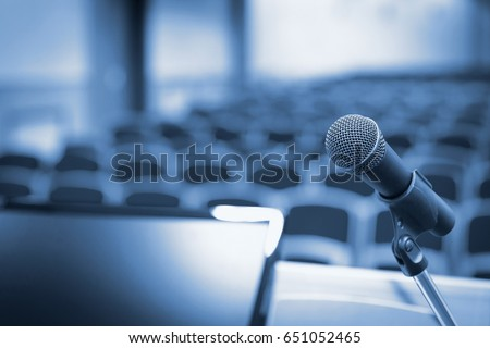 Rostrum with microphone and computer in conference hall #651052465
