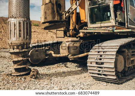 Rotary drills working and making holes in the ground on Highway construction site for viaduct and bridge