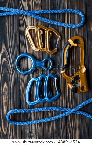 Rotated picture. Isolated photo of climbing equipment. Parts of carabiners lying on the wooden table.