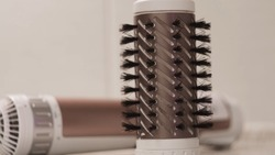 Rotating brush on hair dryer. Concept. Close-up brush with bristles for Curling and drying hair. Hair dryer Curling brush on white isolated background