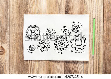 Rotating gears pencil hand drawn. Mechanical technology and machine engineering symbol. Engine mechanism with cogwheels sketch on wooden surface. Workplace with paper and pencil on wooden desk. #1420733516