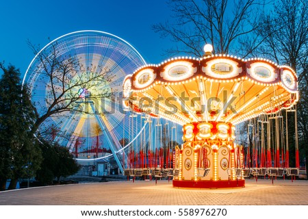 Rotating Illuminated Attraction Ferris Wheel And Carousel Merry-go-round On Summer Evening In City Amusement Park. #558976270