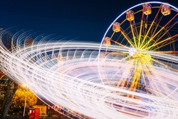 Rotating In Natural Motion Effect Illuminated Attraction Ferris Wheel On Summer Evening In City Amusement Park.