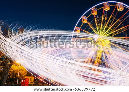 Stock Photo Rotating In Natural Motion Effect Illuminated Attraction Ferris Wheel On Summer Evening In City Amusement Park.
