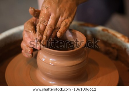 Rotating potter's wheel and clay ware on it taken from above. A sculpts his hands with a clay cup on a potter's wheel. Hands in clay. Process of. Side view