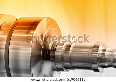 Rotating spindle of turning lathe and metal detail. Selective toning.