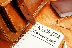 Roth ira conversion memo near retro briefcase and glasses.