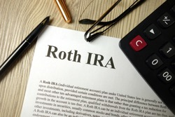 Roth IRA mockup with calculator pen and glasses, retirement planning concept