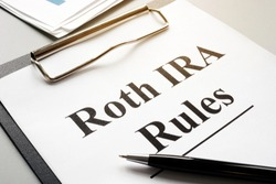 Roth IRA rules with stack of papers and pen.