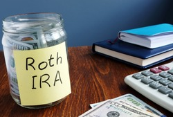 Roth ira written on a label of the jar with money.