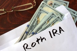 Roth IRA written on an envelope with dollars. Savings concept.