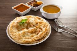 Roti Parata or Roti canai with lamb curry sauce - popular Malaysian breakfast