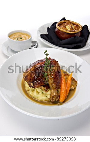 Rotisserie roasted chicken leg served over mashed potatoes with baby carrots and a gravy sauce.  A fresh green sprig of rosemary tops this off.  Warm bowls of soup are featured in the background.