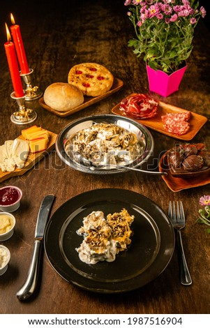 Rotolo with shredded ribs and funghi with milk cream on a black plate on a romantic dinner table. Gourmet. Valentine's day. Foto d'archivio ©