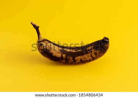 Rotten banana on yellow background. Excessive consumption concept. Foto stock ©