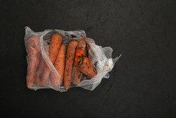 Rotten carrots in plastic bag. Ugly moldy vegetable. Improper food storage. Concept - reduction of organic waste. Dark background, space for text.