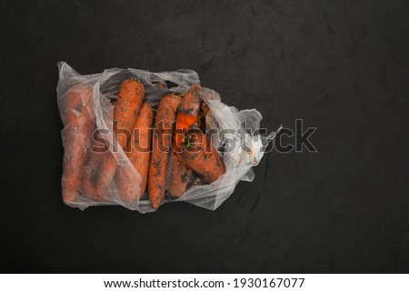 Rotten carrots in plastic bag. Ugly moldy vegetable. Improper food storage. Concept - reduction of organic waste. Dark background, space for text. Foto stock ©