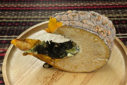 Rotten pumpkin on the wooden plate. Fungus and yeast on the piece of pumpkin.  Infected vegetable by fungi in the kitchen.