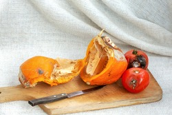 Rotten smashed Pumpkin with two rotten Tomatoes and Knife on wooden Board in white background