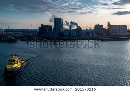 ROTTERDAM, NETHERLANDS - MAY 30, 2014: A tugboat is approaching the viewer in the port of Rotterdam on May 30, 2014 in Rotterdam, the Netherlands. With about 105 square kilometres and a stretch of