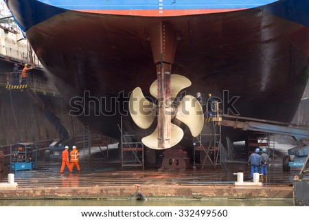 ROTTERDAM, NETHERLANDS - SEP 5, 2015: Workers removing algue in ship repair dry dock.