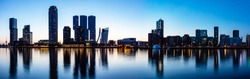 Rotterdam skyline night panoramic view. City towers illuminated panorama, reflections on the river Maas water, sunset time, blue clear sky, summer evening