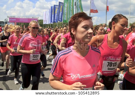 ROTTERDAM, THE NETHERLANDS - JUNE 10 2012: Female runners dressed in pink passing close bye running in the annual Ladiesrun 10 KM event held on Sunday June 10,  2012 in Rotterdam.