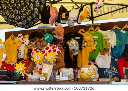 ROUEN, FRANCE - JULY 5 : A young man selling various promotional items on the official Tour of France shop in Rouen during the stage 5 of Le Tour de France on July 5, 2012.