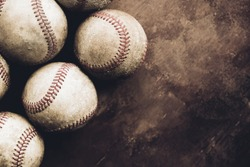 Rough and rugged texture of old baseball balls close up on brown vintage background, copy space for sport.