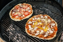 Rough home made pizza with tomatoes, basil and salami made on grill
