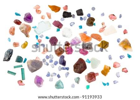 Rough precious and semi-precious stones - ruby, sapphire, emerald, tourmaline, opal, apatite, aquamarine, iolite, spinel. Isolated on white.