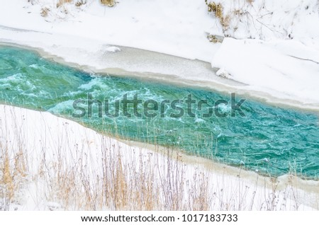 Rough river at the foot of the mountains in a turquoise, blue, green forest in winter, ice and snow around the landscape #1017183733