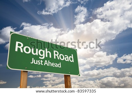 Rough Road, Just Ahead Green Road Sign Over Dramatic Sky, Clouds and Sunburst.
