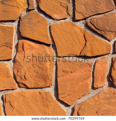 Rough sandstone and mortar wall background texture pattern.