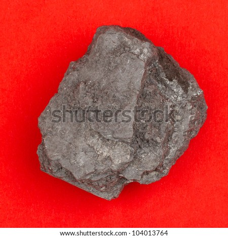Rough specimen of black coal, a combustible sedimentary rock on a red background
