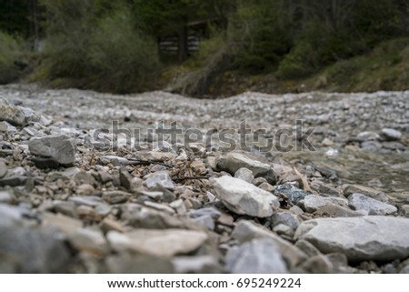 Rough stones and rock chips on the ground viewed low angle with copy space above in an outdoor rural environment