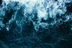 Rough stormy blue ocean waves with white foam, aerial view.