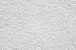 Rough surface of a concrete wall painted in greyish white, concrete wall background, blurred white background.