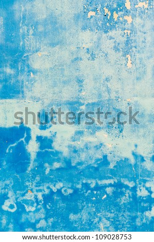 Rough textured blue wall with stains