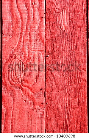 Rough textured red painted wooden boards.  Sunshine makes red vibrant.