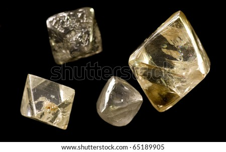 rough uncut diamonds showing crystalline structure, facets and imperfections on a black background