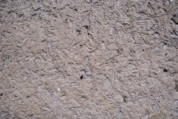 Rough weathered surface of mud daub on a wall used as a natural cladding over a timber frame in a full frame texture