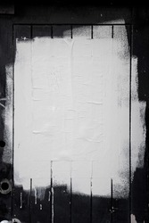 Rough white paint rolled over a black wooden textured background