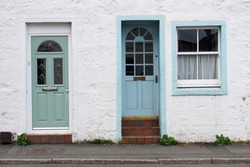 Rough white wall with green and blue door with window