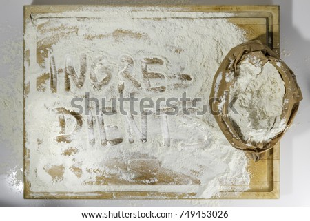 Rough wooden rectangular used cutting board background with paper sack of flour and ingredients word inscribed with finger directly from above on white background #749453026
