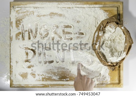 Rough wooden rectangular used cutting board background with paper sack of flour and ingredients word inscribed with hand directly from above on white background #749453047