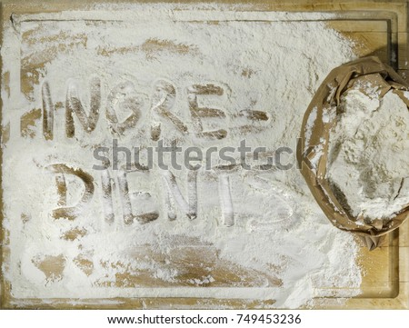 Rough wooden rectangular used cutting board background with paper sack of flour and ingredients word inscribed with finger directly from above #749453236