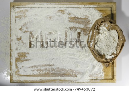 Rough wooden rectangular used cutting board background with paper sack of flour and menu word inscribed with finger directly from above on white background #749453092