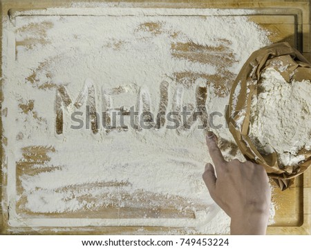 Rough wooden rectangular used cutting board background with paper sack of flour and menu word inscribed with finger directly from above #749453224
