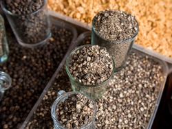 Roughly cracked black peppercorns alongside black peppercorns and fried minced garlic and a local market in the Philippines. Closeup shot.